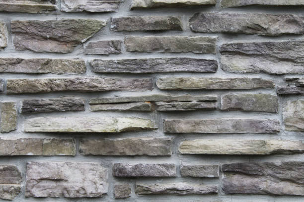 dark grey black and white thin cut stacked stone block wall with shadows and straight lines suitable for website background marketing backgrounds backdrops architecture architectural layout design stock photo