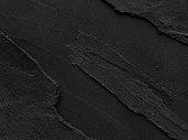istock Dark grey black slate with rough background. 1054200786