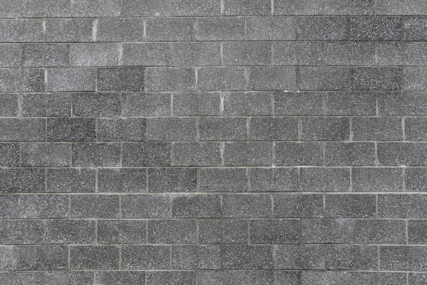 dark grey large stone tall block wall light gray color grout with shadows and straight lines suitable for website background marketing backgrounds backdrops architecture architectural layout design stock photo