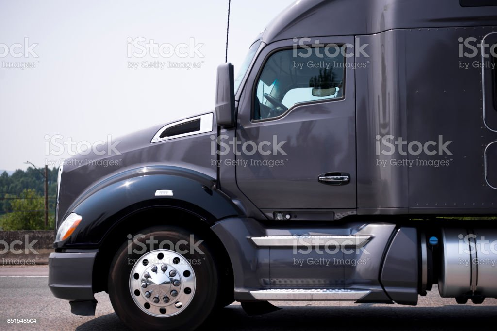 Dark grey modern big rig semi truck tractor profile stock photo