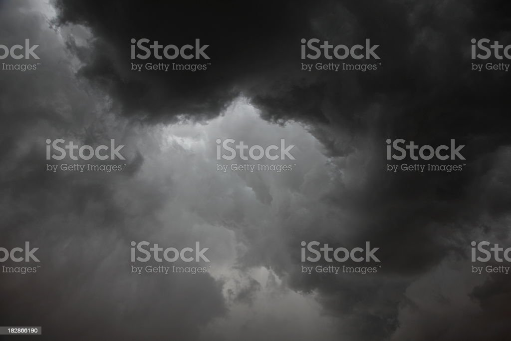 Dark grey storm clouds with limited light royalty-free stock photo