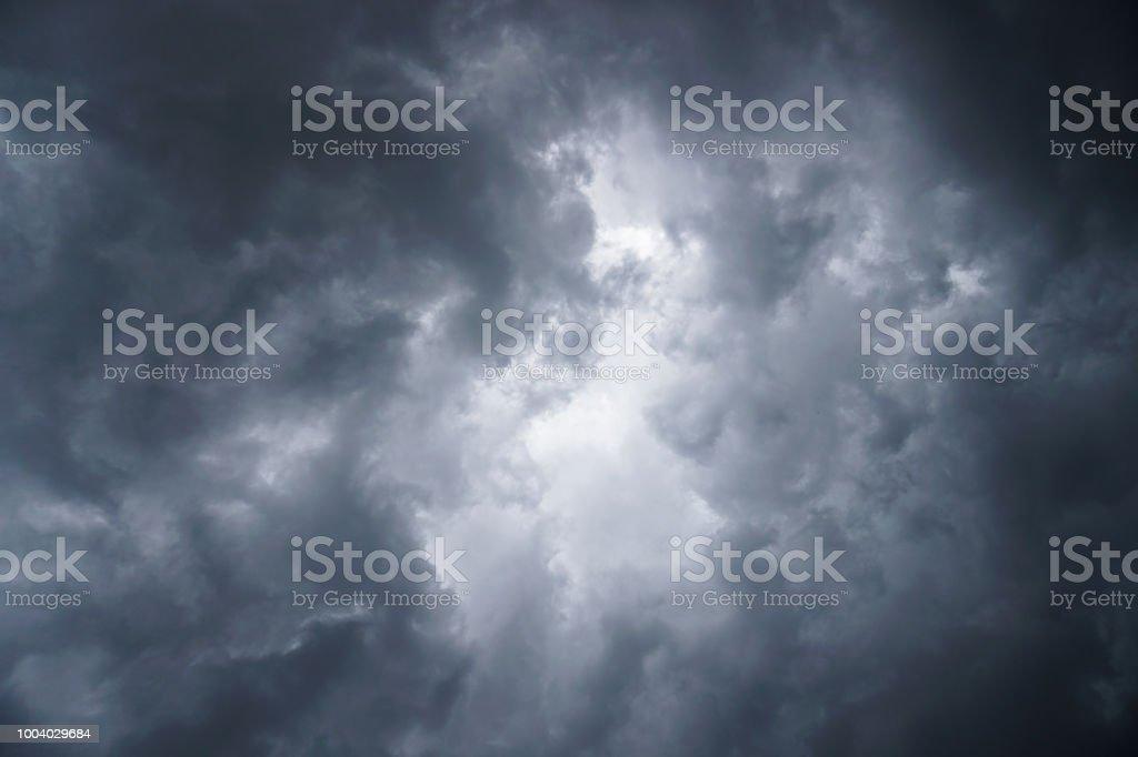 Dark, grim, stormy, rainy sky with rays of light. Scary hurricane...
