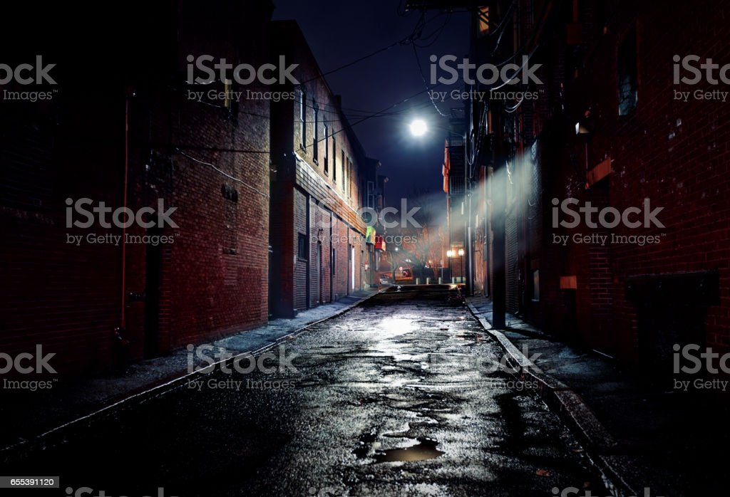 Dark Gritty Alleyway Long dark gritty alley between two old derelict buildings at night. Rain sodden pavement with eerie mist. Brickwork walls frame the ominous and dangerous inner city alleyway Alley Stock Photo