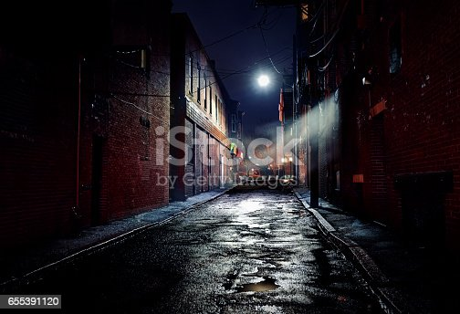 Long dark gritty alley between two old derelict buildings at night. Rain sodden pavement with eerie mist. Brickwork walls frame the ominous and dangerous inner city alleyway