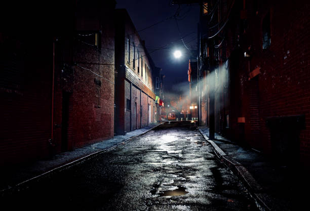 Dark Gritty Alleyway Long dark gritty alley between two old derelict buildings at night. Rain sodden pavement with eerie mist. Brickwork walls frame the ominous and dangerous inner city alleyway alley stock pictures, royalty-free photos & images