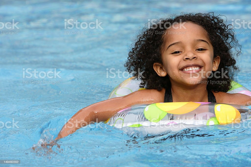 Dark haired girl swimming with a rubber ring stock photo