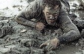 Dark haired man crawling during a mud run