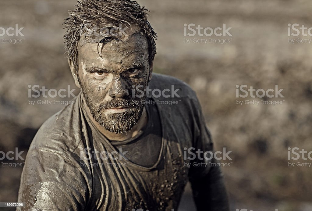 Dark haired man posing during a mud run stock photo
