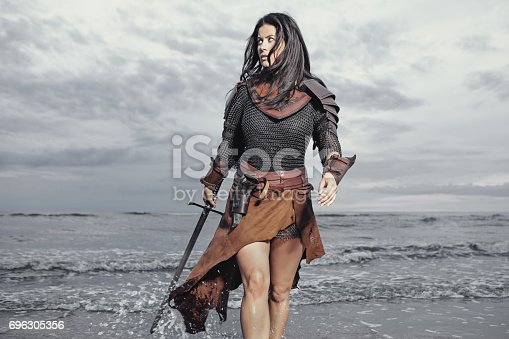 istock Dark Haired Viking Woman in the Sea at Dusk 696305356