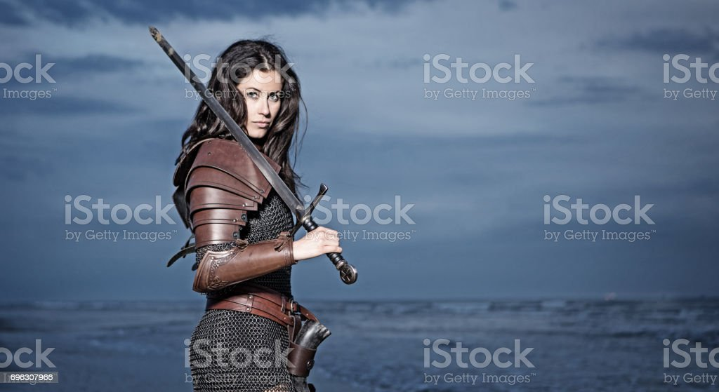 Dark Haired Viking Woman in the Sea at Dusk stock photo