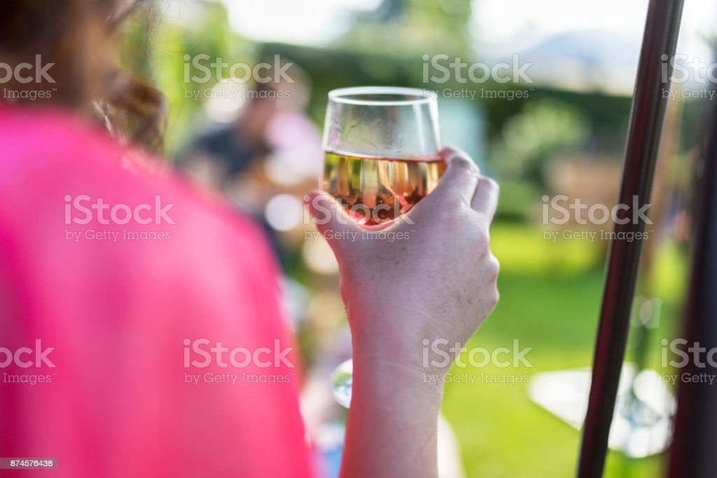 Dark haired woman drinking wine at a summer get together in the UK stock photo