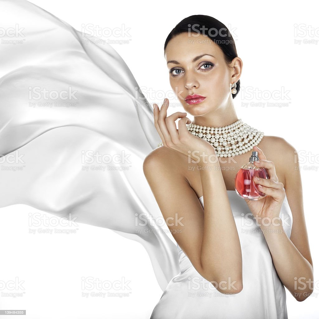 Dark haired woman in pearls and a white dress with perfume royalty-free stock photo