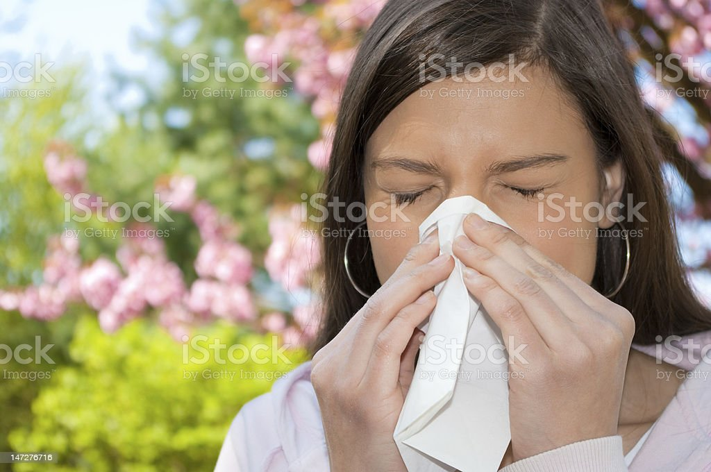 Dark haired woman sneezing on a Spring day near flowers A young woman with a allergy sneezing into handkerchief, with flowering plants in the background. Adult Stock Photo