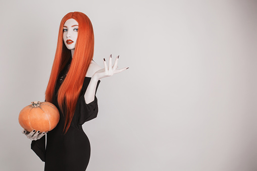 Dark halloween costume. Autumn gothic sale. Woman vampire with red hair in black dress holding pumpkin. Model with red lips advertise product. Gothic look. Halloween sale. Model advertise cosmetics
