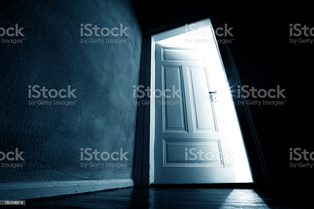 Dark hallway with an opened door with bright light coming in stock photo