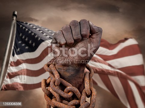 Dark hand in chains with American flag behind