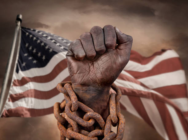 Dark hand in chains with US flag behind stock photo