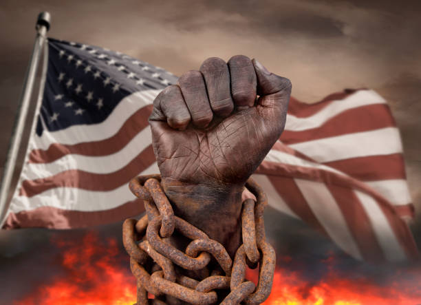 Dark hand in chains with US flag stock photo