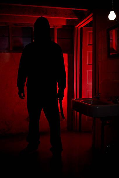 Escuro com capuz Killer com faca no subsolo, espaço para texto - foto de acervo