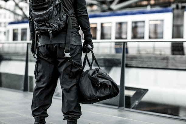 Dark hooded terrorist figure at public transport hub Dark hooded male terrorist like figure at urban city public transport hub terrorism stock pictures, royalty-free photos & images