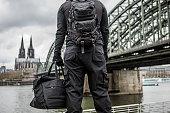 Dark hooded terrorist figure in empty urban surroundings