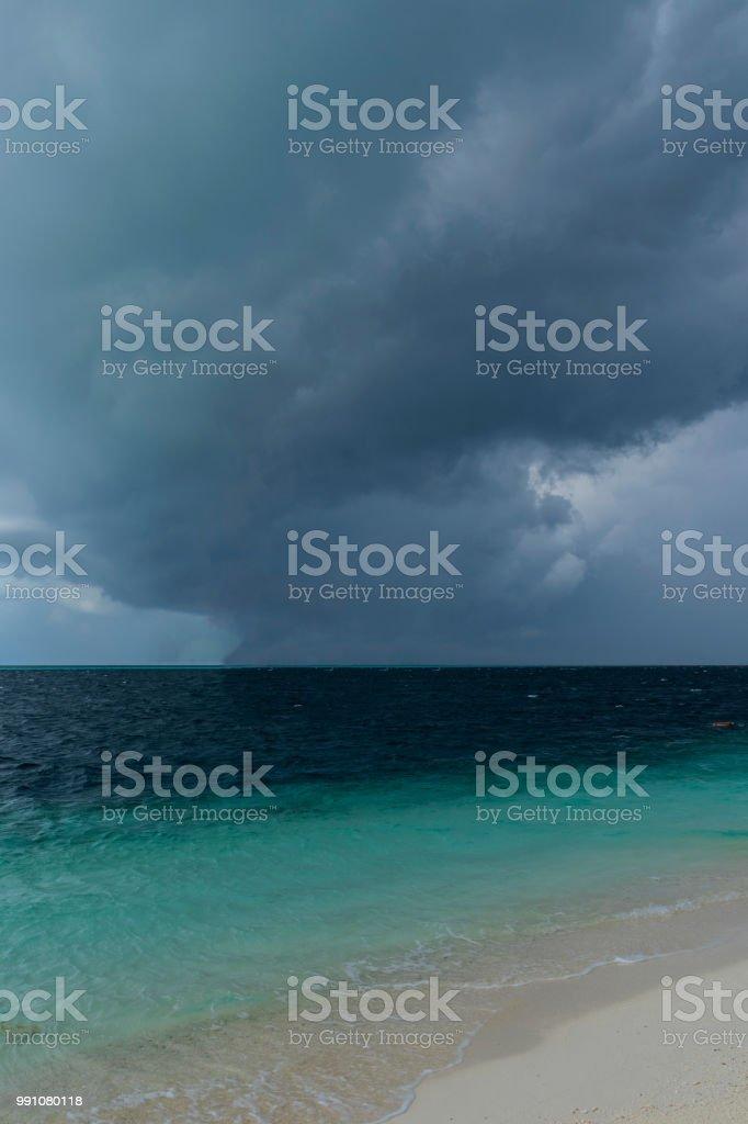 Dark hurricane cloud above tropical sea