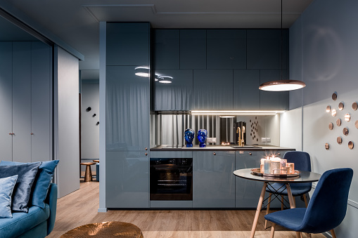 Dark home interior in blue with open kitchen and dining area with round table