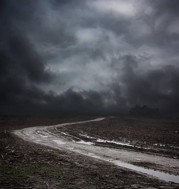 Dunkle Landschaft mit schmutzigen Straße und der Moody Sky – Foto