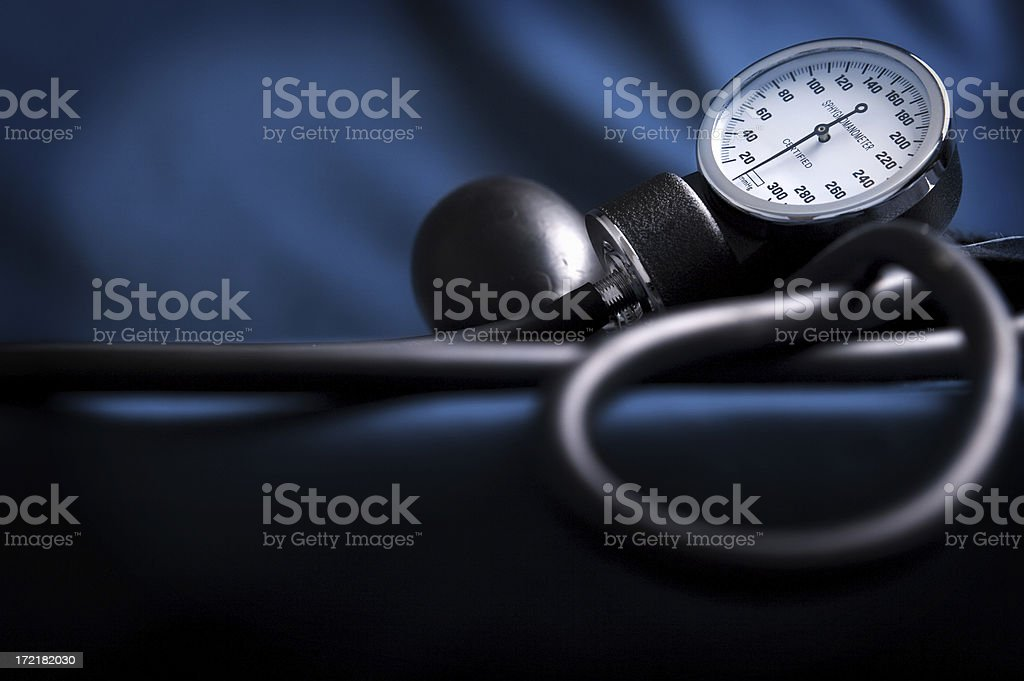 Dark lit picture of a sphygmomanometer laying on blue cloth royalty-free stock photo