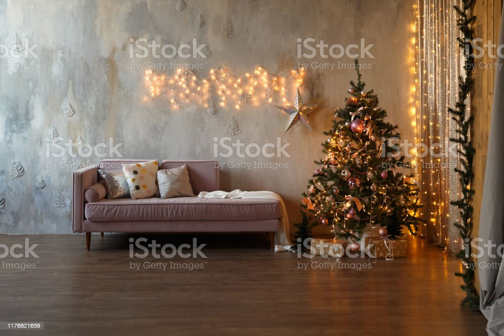 Dark loft living room decorated for Christmas with tree and lights.