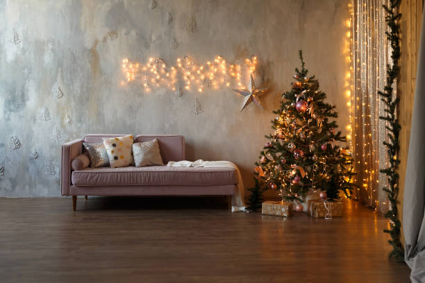 Dark loft living room decorated for Christmas with tree and lights stock photo