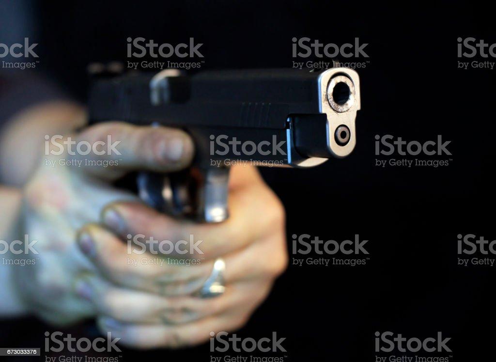 Dark man pointing a gun looking at the camera stock photo