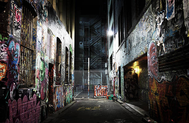 Dark Melbourne alleyway filled with graffiti One of numerous alleyways in Melbourne city, full of graffiti, obscure and intimidating. At the centre of the shot steel fire escape stairs can be seen. alley stock pictures, royalty-free photos & images