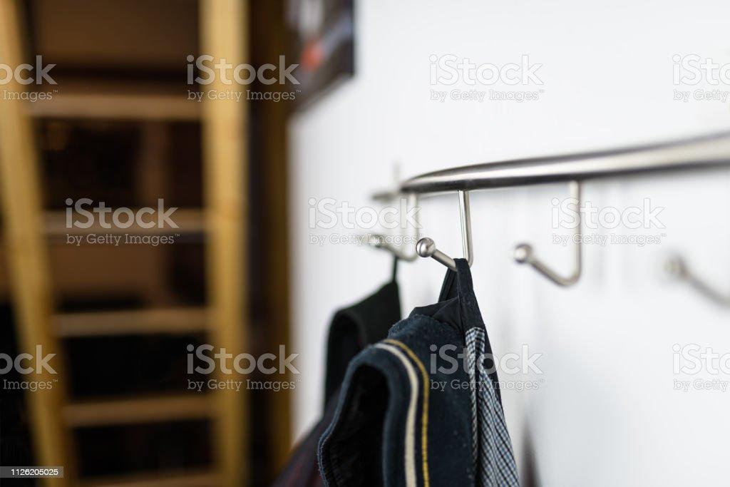 Dunklen Herren Jacken aufhängen an einem Haken im Haus, auf eine Wand aufhängen. – Foto