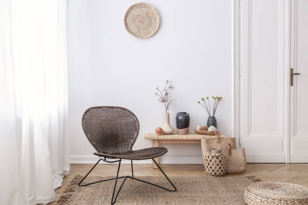 Dark, modern wicker chair in a white living room interior with a wooden bench and decorations made from natural materials Dark, modern wicker chair in a white living room interior with a wooden bench and decorations made from natural materials wicker stock pictures, royalty-free photos & images