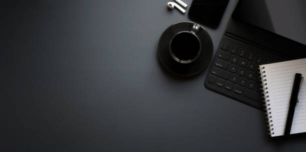 Dark modern workplace with tablet, a cup of black coffee