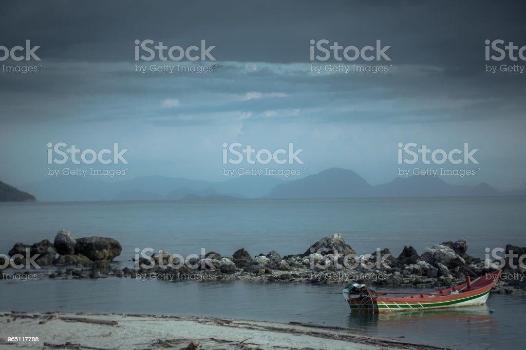 Dark moody tranquil landscape tropical beach sunset island sea boat zbiór zdjęć royalty-free