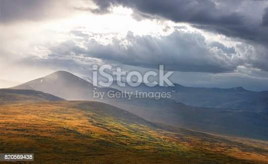 istock Dark mountain under a stormy evening dramatic cloudy sky with dark clouds and bright rays of sunset light Plateau Ukok Altai mountains Siberia Russia 820569438