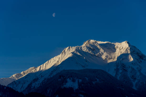 Dark mountain with sunlit snowy top - the moon is visable in early afternoon stock photo