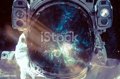 istock Dark nebula and stars in space, reflection on the spacesuit helmet. Adventure of spaceman. Astronaut in outer space. Elements of this image furnished by NASA. 1056814432