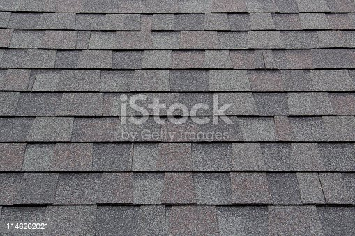 istock dark new roof shingle background and texture. asphalt tiles of house roof. 1146262021