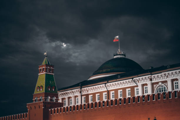 Dark night shot of Russian Kremlin: Senate dome, tower, wall Night shot: Kremlin Moscow Dome of Senate building, a red Kremlin wall, flag of Russia with the emblem on it; sinister dark sky with a moon partly closed by the clouds kremlin stock pictures, royalty-free photos & images