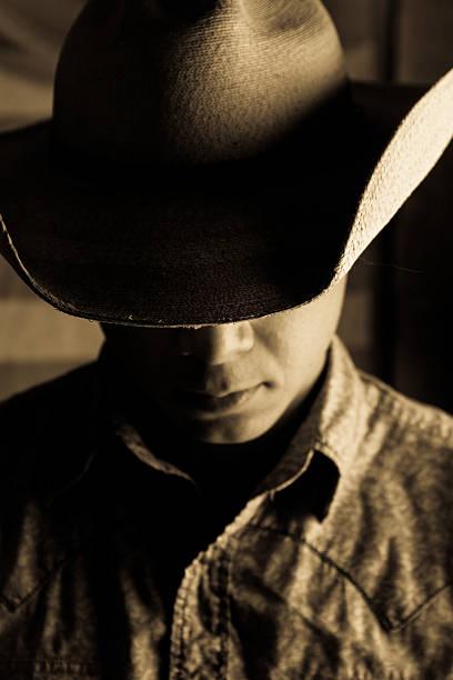A dark portrait of a man wearing a cowboy hat stock photo