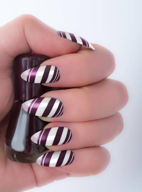 dunkel lila gestreiftes stiletto nail fashion trends winter - nails stiletto stock-fotos und bilder