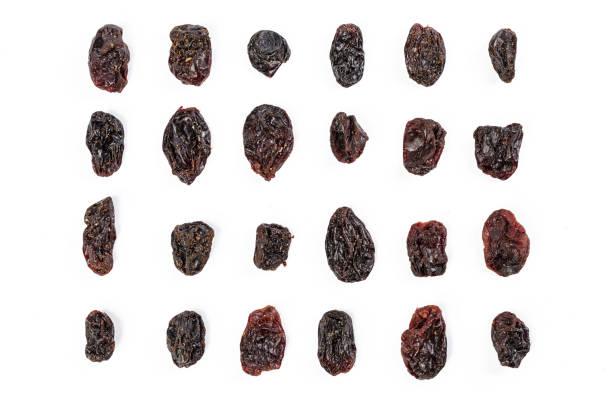 dunkle rosinen isoalted auf weißem hintergrund - grape sugar stock-fotos und bilder