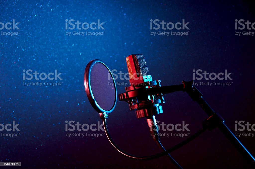 A dark recording studio with a microphone stock photo