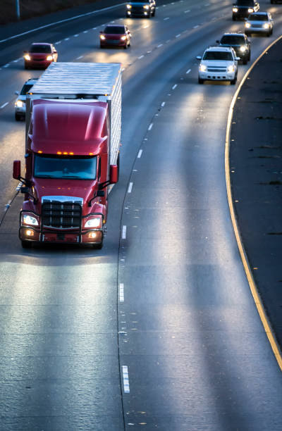 Dark red big rig semi truck transporting cargo in refrigerator semitrailer running on the wide multilines highway at night with turned on headlights stock photo