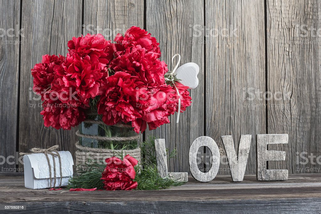 Dark red peonies in a decorated glass jar stock photo