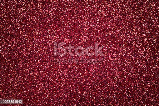 Dark red sparkling background from small sequins, closeup. Brilliant shiny backdrop from textile. Shimmer wine paper with vignette