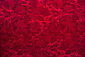 Dark red textile wallpaper on the wall